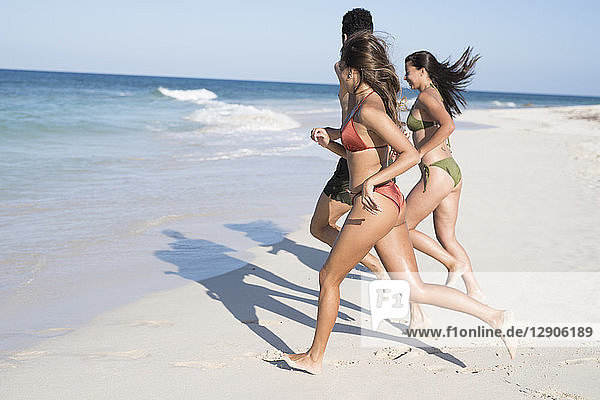 Happy carefree friends running on the beach to the sea