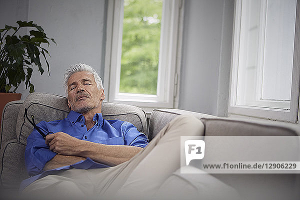 Portrait of mature man relaxing on couch at home