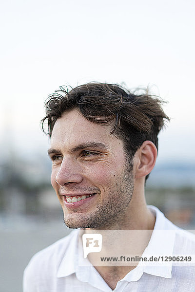 Portrait of smiling young man with tousled hair outdoors