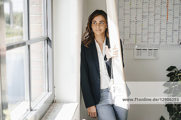 Woman standing in office  looking out of window
