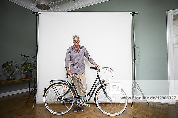 Portait of mature man posing with bicycle at projection screen