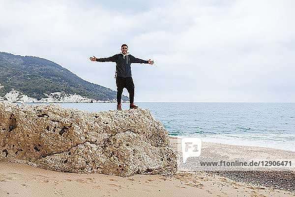 Italy  Vieste  relaxed man with arms outstretched standing on a rock on Vignanotica Beach