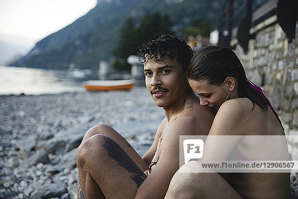 Affectionate young couple relaxing after taking a bath in a lake