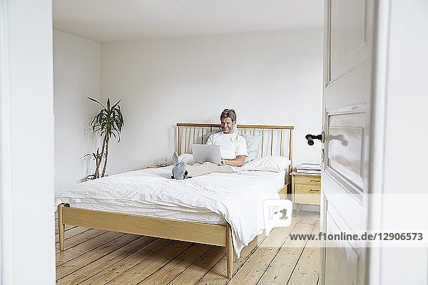 Mature man relaxing with laptop in bedroom