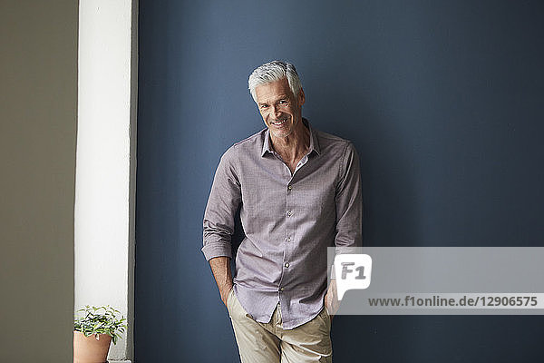 Portrait of confident mature man at home leaning against blue wall