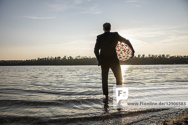Back view of businessman with beach ball standing at lakeshore watching sunset