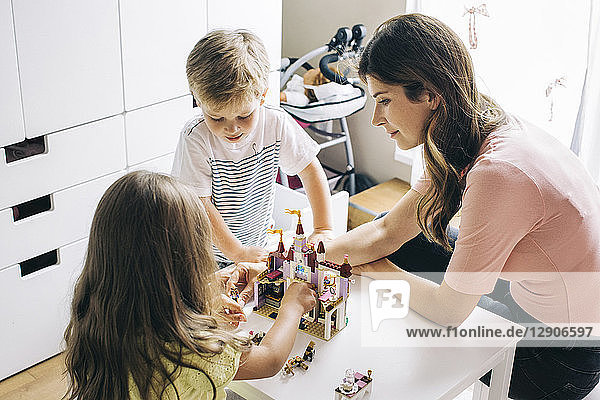 Mother with two children building up toy castle at home