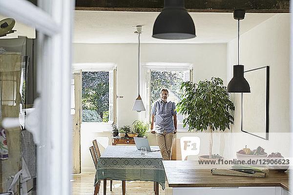 Mature man standing in his dinig room  portrait