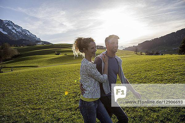 Austria  Tyrol  Walchsee  happy couple hiking on an alpine meadow