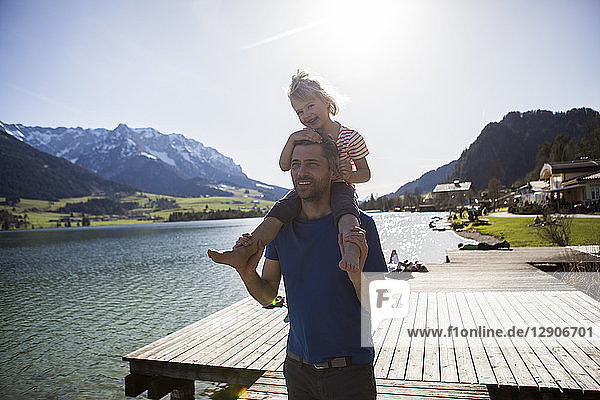 Austria  Tyrol  Walchsee  happy father carrying daughter on shoulders at the lake
