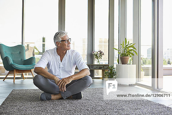 Mature man sitting on carpet at home looking out of window