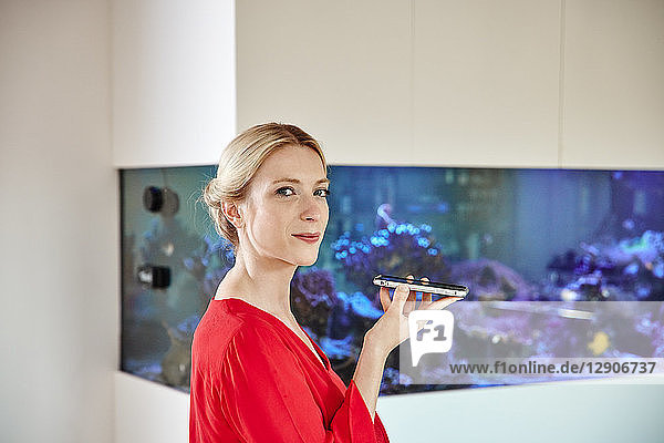 Young woman holding smartphone in office with an aquarium