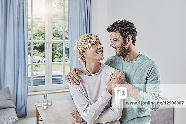 Portrait of happy couple embracing at home