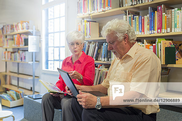 Senior couple with laptop and book in a city library