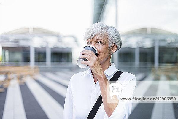 Senior businesswoman in the city drinking coffee
