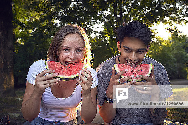 Young couple sitting in park  eating watermelon