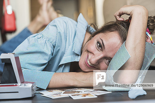 Portrait of happy young woman lying on the floor with instant photos