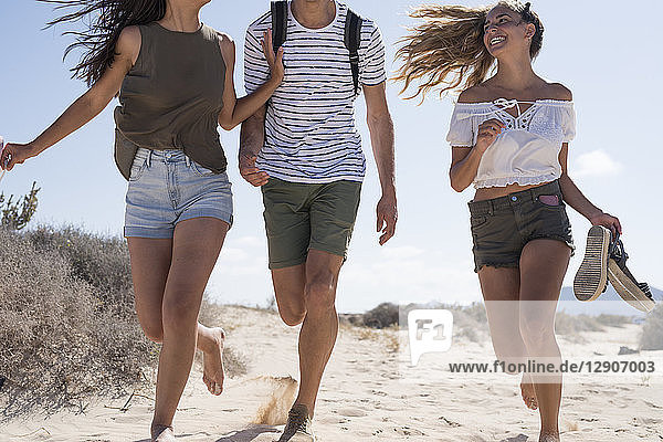Friends having fun  running barefoot on the beach