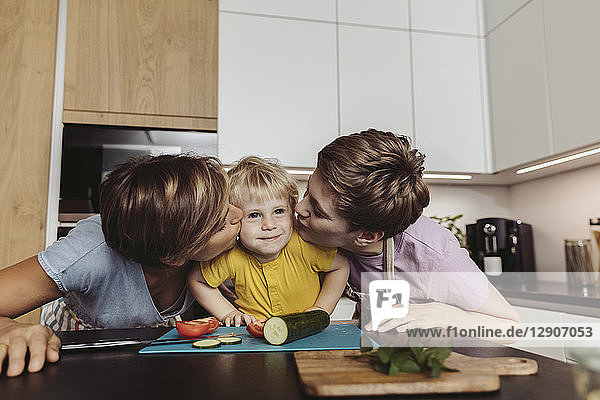Happy lesbian couple kissing their child in kitchen