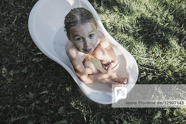 Portrait of little girl sitting in bath tub in garden