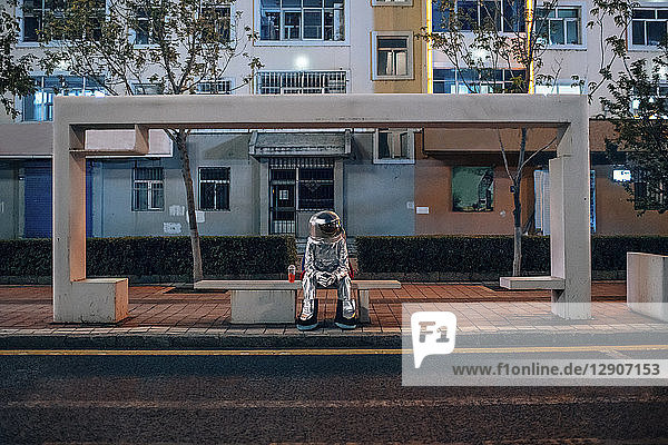 Spaceman sitting on bench at a bus stop at night with soft drink