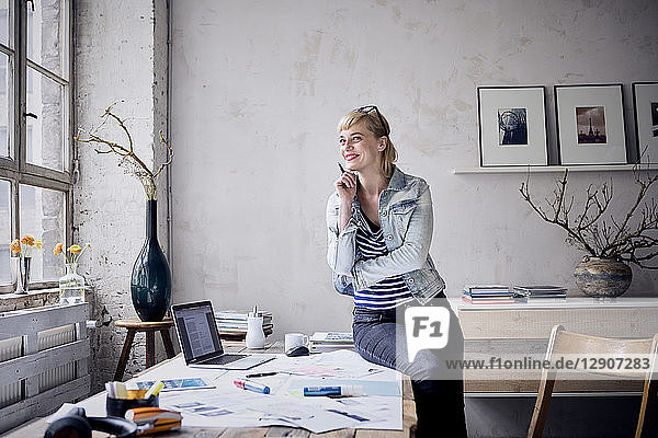 Portrait of smiling woman at desk in a loft