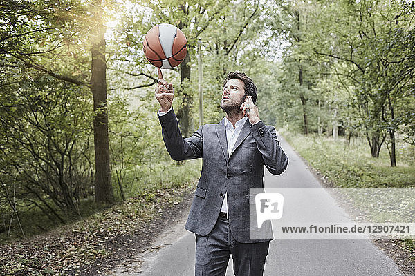 Businessman balancing basketball and talking on smartphone on rural road