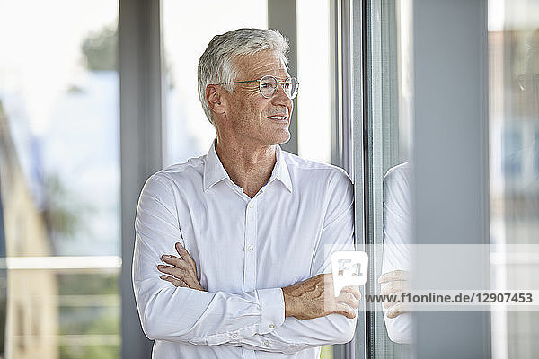 Businessman in office leaning against window  with arms crossed
