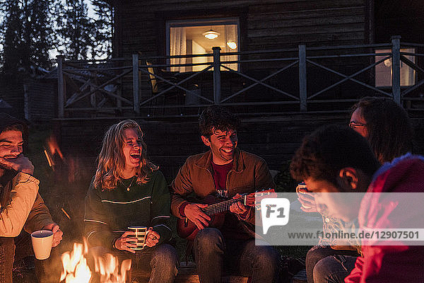 Group of friends sitting at a campfire  talking and playing guitar