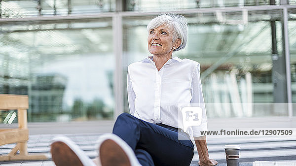 Smiling senior businesswoman sitting outside looking around