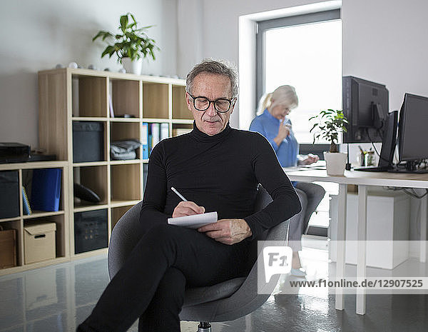 Senior man sitting in office taking notes with colleague working behind him