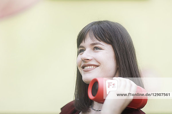Young woman carrying bluetooth loudspeaker  listening music