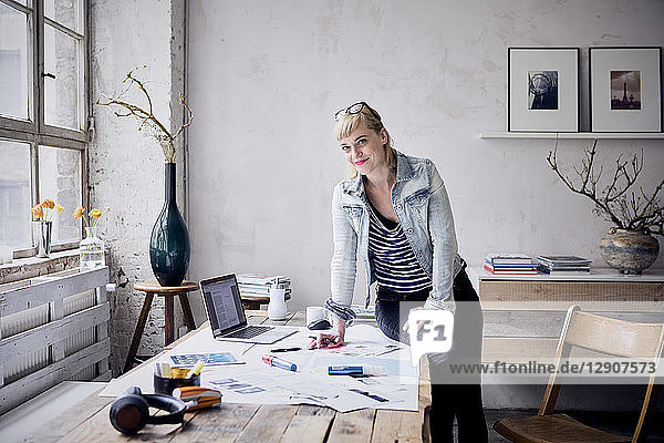 Smiling woman at desk in a loft