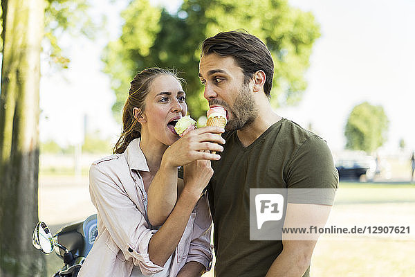 Couple with motor scooter in summer sharing ice cream