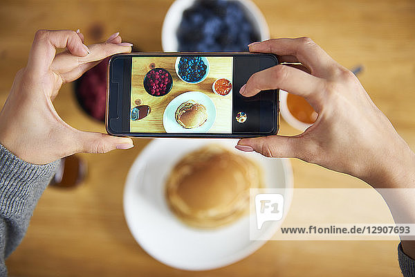 Young woman taking pictures of breakfast pancakes with berries and fresh fruit
