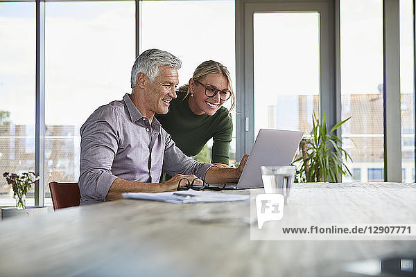 Smiling mature couple using laptop on table at home