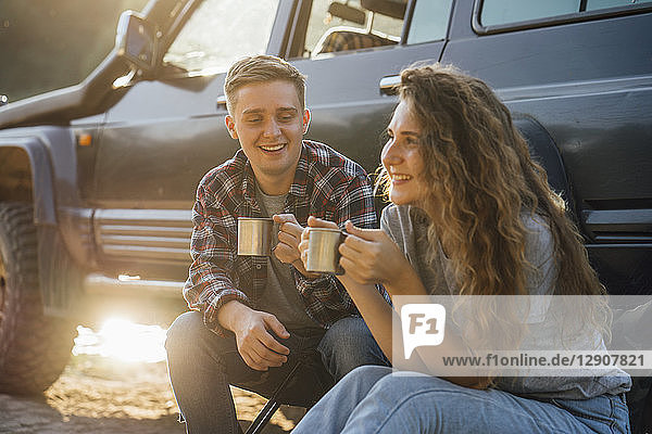 Young couple sitting by car  taking a break  drinking tea