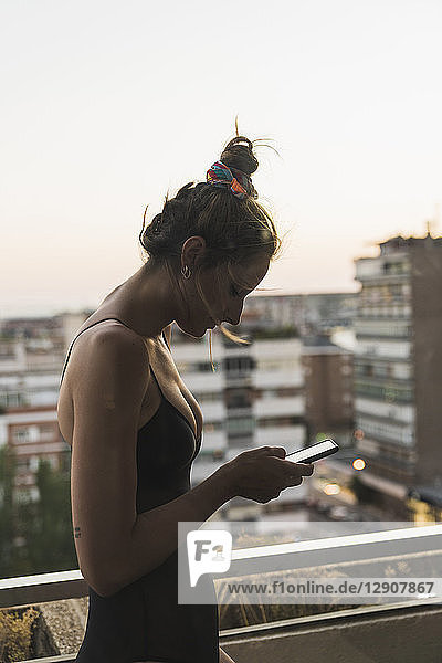 Young woman wearing black dress using cell phone on balcony