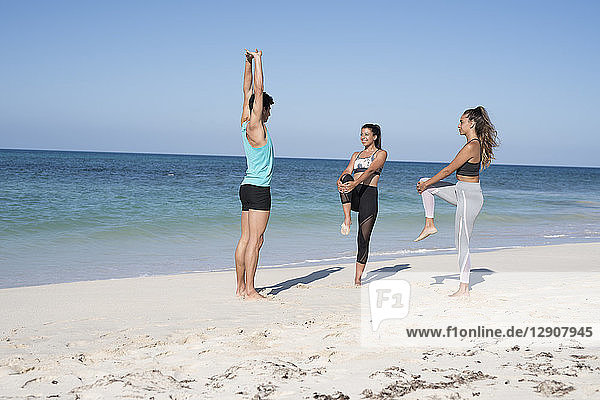 Spain  Canary Islands  Fuerteventura  two young women and young man exercising on the beach