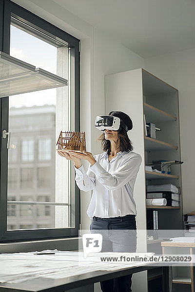 Woman holding architectural model of house  using VR glasses