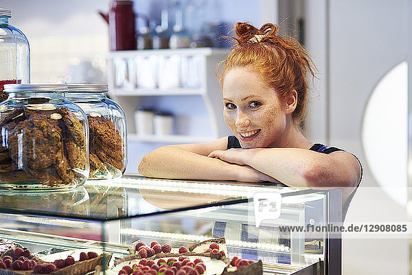 Portrait of smiling young woman at the cake display in a cafe