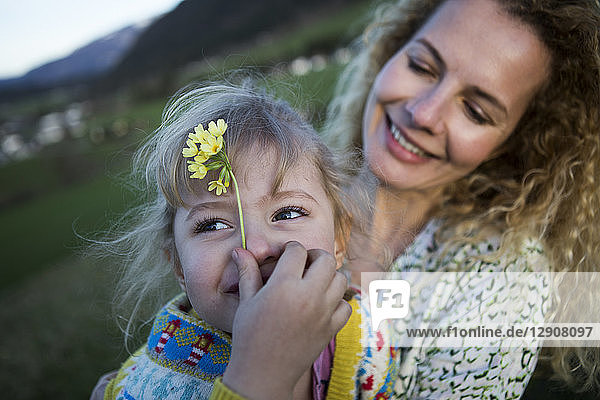 Happy mother and daughter with flowers on a meadow
