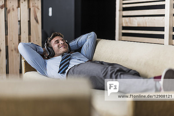 Businessman with headphones lying on couch in office lounge