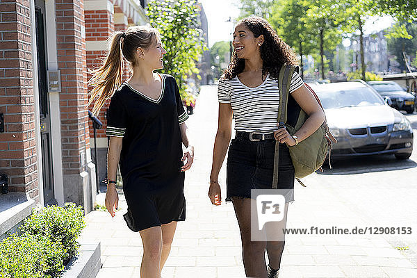 Two laughing girlfriends walking in the city