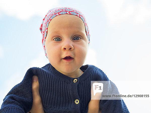 Portrait of amazed baby girl against sky