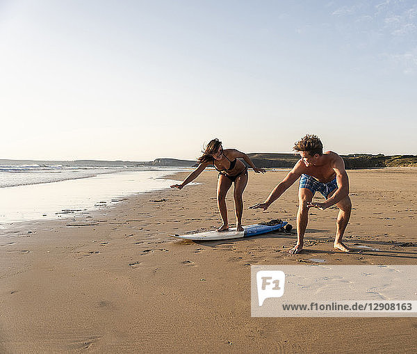 Young man showing young woman how to surf on the beach