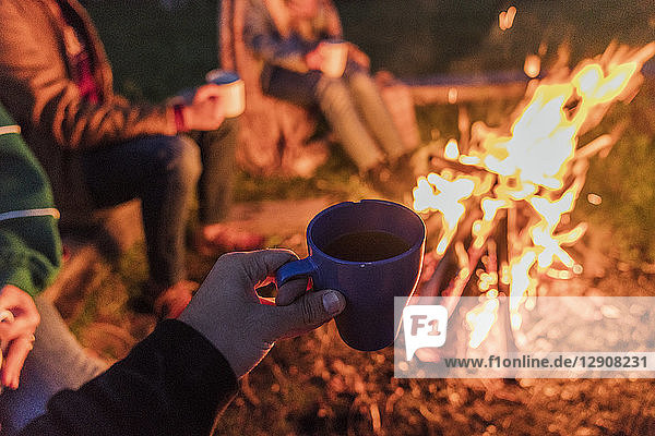 Hand of person holding tea cup,  group of people sitting at a camp fire