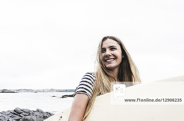 Young woman on the beach carrying surfboard  portrait