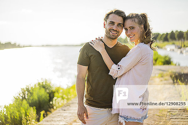 Portrait of smiling affectionate couple standing at the riverside in summer