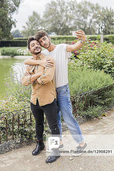 Portrait of young gay couple taking selfie with smartphone at city park